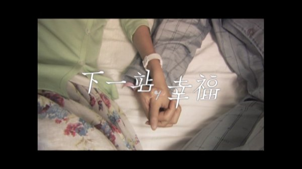 Ren Guangxi and Liang Mucheng hold hands on a bed while the screen says 'Next Stop, Happiness'