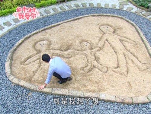 Cunxi draws a family in a sandbox.