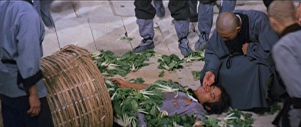 San Te arrives at Shaolin Temple in a basket full of vegetables.