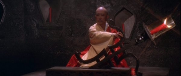 The monk moves a candlestick back and forth.