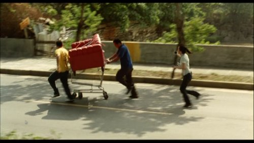 A reporter chases Manuel and Dado, who are pushing the sofa on a shopping cart