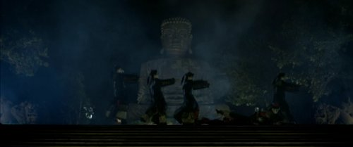 A bunch of ... monks? ... collapsing in front of a Buddha at night