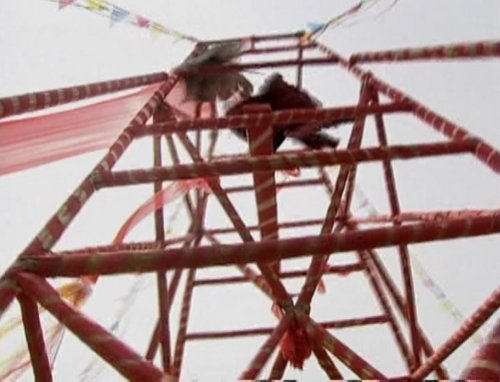 The two characters fight their way down the collapsing scaffolding