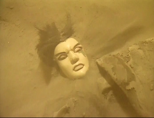 A puppet is buried in sand.
