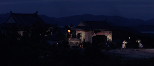 A temple at night with hills and a harbor in the background.