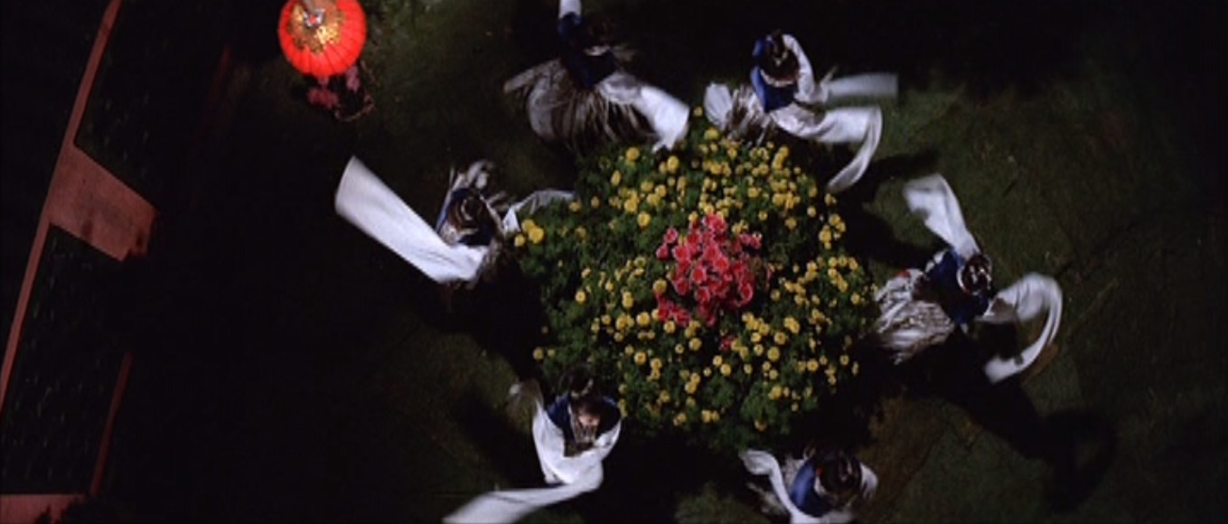 Six beautifully dressed women dance in a circle around a flower bush in a shot from overhead.
