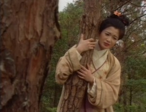 Yue Lingshan looks very unhappy as she hugs a pine tree.