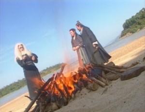 Linghu Chong, Xiang Wentian, and Ren Woxing by a bonfire on the beach.