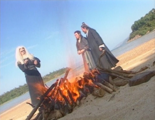 Linghu Chong, Xiang Wentian, and Ren Woxing by a bonfire on the beach.